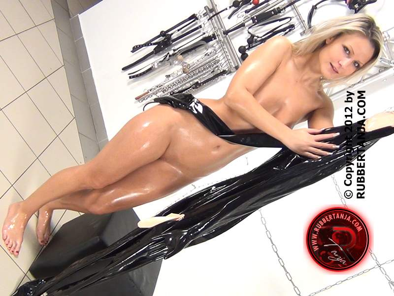 Picture #2 of Beautiful blonde covers herself in oil and then puts on a skin-tight rubber full-body costume
