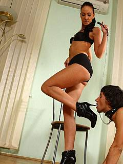 Mistress Jade is using a whip to control her sub who is currently busy lickung her toes