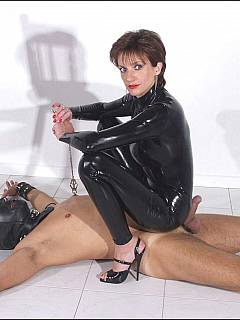 Masked slave enjoys latex MILF trampling him in high heel shoes