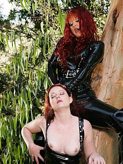 Redhead mistress and her sub are dressed in rubber and enjoying spanking in the forest