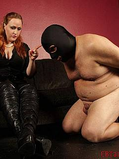 Fat guy is bent over the knee and spanked by the redhead dominatrix