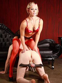 Mistres in red lingerie is enjoying male crawing while his balls are locked in clamping device