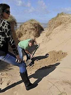 Bizarre femdom scenario where guy digs the hole in the ground and the girl is burying him leaving just the head above