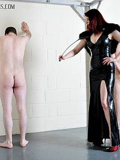 Sissy boy provides the sitting space for the dominatrix in black rubber dress