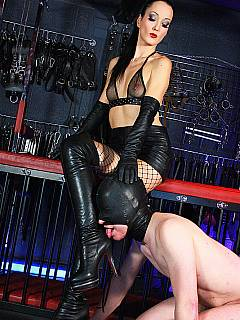 Babe in fishnets and high heel boots is riding the slave after he licked her shoes like a slut