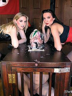 Male slave is put in a box by two girls, his mouth is open and bitches are feeding him with cum from used condoms