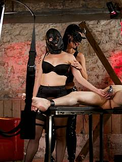 Dominatrix in the mask is controlling a couple: male is bound and cock-caged while the sungirl is spanked
