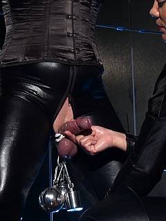 Lady and her slave are both dressed in black rubber: male is in bondage and tormented by the dominant plumper