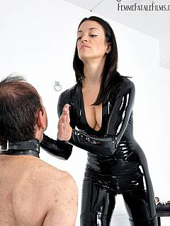 Babe is shiny latex costume is using a whip to punish handcuffed man