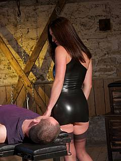 Dominant brunette is in the BDSM dungeon, tormenting cock being pantie-less and dressed up in rubber