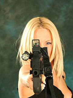 Bikini model with an automatic gun looks both: sexy and eerily