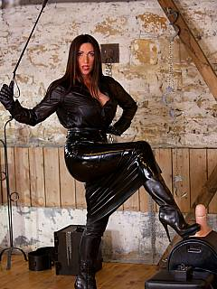 Dominatrix in leather is expecting new femdom slave to be delivered to the BDSM chamber