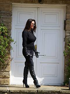 Dominatrix in blak satin is out for a walk holding a whip in her hands and exposing tasty bits of her body in the sunlight