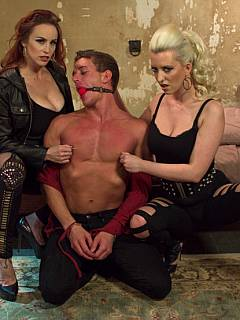 A couple of passionate lesbian dommes are sharing one bound man in this BDSM orgy