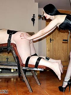 Dominatrix in corset shoving huge strapon in slave's ass after strapping him to BDSM rack
