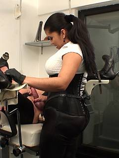 Sissy is bound in the medical chair: his legs are spread wide for the dominatrix to be easy destroying his ass with strapon