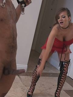 Domme girl locked slave in a steel spreadbar and lashing his cock with a small whip