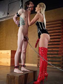 Handcuffed male is bent forward and ass-fucked by hot blonde while his balls are chained