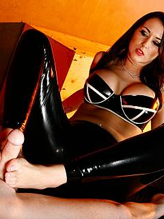 Redhead is teasing slave with a footjob while wearing glossy rubber leggings