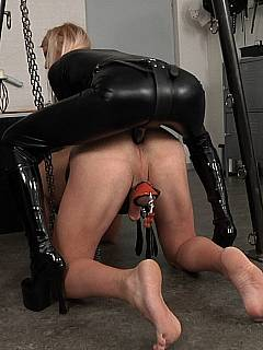Bitch in leather has a male put in love swings and bangs his ass with strapon dildo