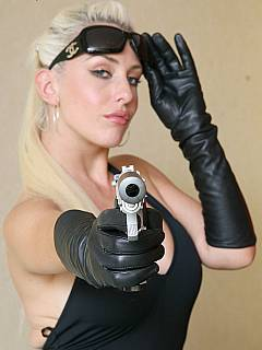 Gorgoues blonde spy is going to distract you with the big boobs and then captivate you with the help of a big gun