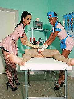 Masked male is lying on top of the medical table looking at a couple of interracial nurses working out his cock in rubber gloves