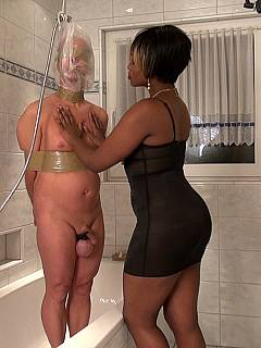 Submissive male is taking a shower under the guidance of a black mistress: bound up with duct tape, water-tortured and not allowed to cum