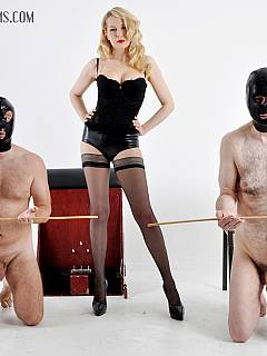 A couple of naked men are controlled by one gorgeous dominatrix with the can in her hands