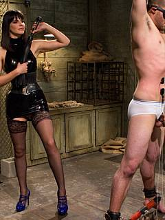 Gorgeous woman in black latex is preparing helpless femdom slave for the first strapon penetration in his life