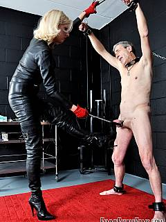 Goddess in catsuit is having male slave naked, spread with chains and torture the sensual spots of his body in red leather gloves