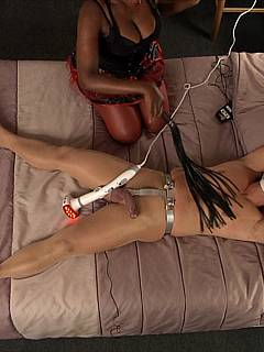 Submissive dude is in bed with black mistress: wearing chastity belt and pantyhose and having his penis crushed with her feet and teased with toys