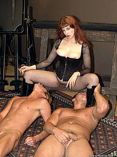 Two guys are controlled by redhead MILF dominatrix: licking her like whores and enjoying BDSM tortures