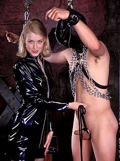 Down in the BDSM chamber there is sexy blonde in latex having nude male put in chains and whipped