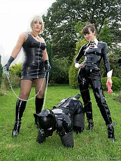 Petboy is wearing full-body rubber costume while being walked on all fours, collared and leashed by two elegant ladies