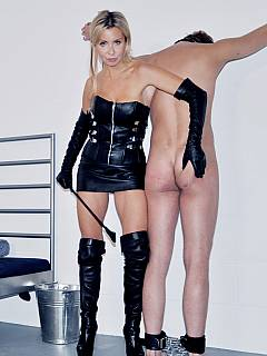 Lady in fur and leather cuffed a sissy and whipping his ass with a cruel smile on her face