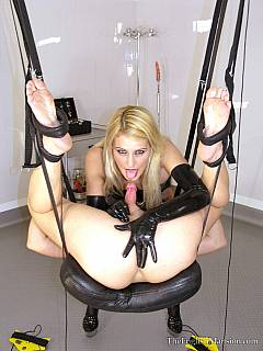 Spread-legged and gas-masked slave in put into love swing so sexy blonde could fuck his ass with the big sex toy