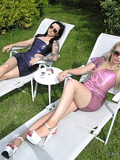 A couple of girls in latex outfits are relaxing in the backyard while cock-harnessed slave is on all fours and stretching his balls trying to reach and lick their feet