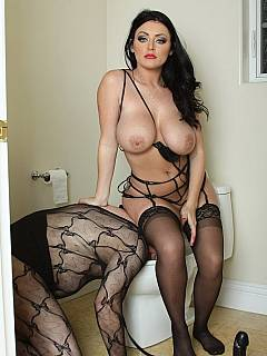 Busty MILF mistress is wearing black PVC lingerie while dominating fishnets-dressed sissy slave
