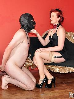 Redhead lady is smoking a cigarette and spitting slave's in his mouth