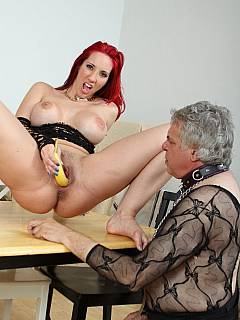 Perverted redhead is making sure banana is covered in pussy juices before feeding in to her slave