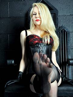 Femdom blond is sitting in her throne down in the BDSM chamber: smoking a cigarette and telling how miserable you are