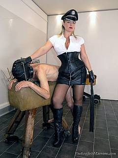 Dominatrix in military-style outfit is showing off her powers over masked femdom slave:  punishing poor man with whipping, spanking and paddling