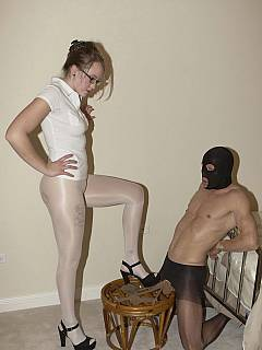 Leggy domme dressed up her slave in nylons, trampling him with her feet and tying up his balls with pantyhose