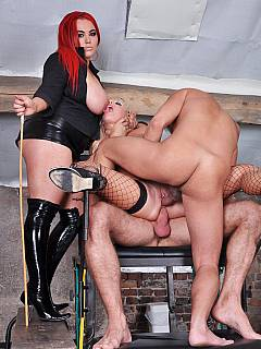 Dominatrix is directing the hardcore threesome scene where a girl in BDSM harness is fucked hard by two femdom slaves