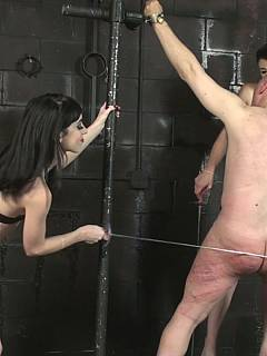 A team of two girls in latex are using sabers as canes to leave marks all over handcuffed slave ass and back