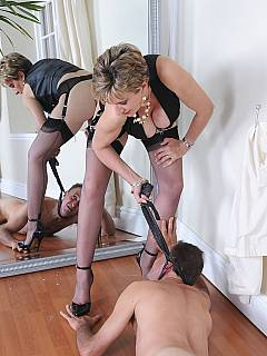 Lady in stockings is using riding crop to control foot-loving slave in front of a big mirror