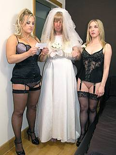 Sissy bride is in doggy-style pose and put in use by two strict ladies armed with strap-on cocks