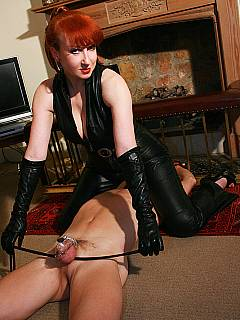 Dominant wife is wearing black leather and keeping her husband locked in chastity device