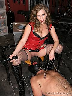 Goddess is sitting in queening stool and channeling electricity to the submissive male balls underneath