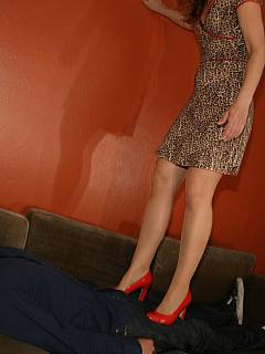 Cruel bitch put on a pair of red high heel shoes to walk along the submissive man